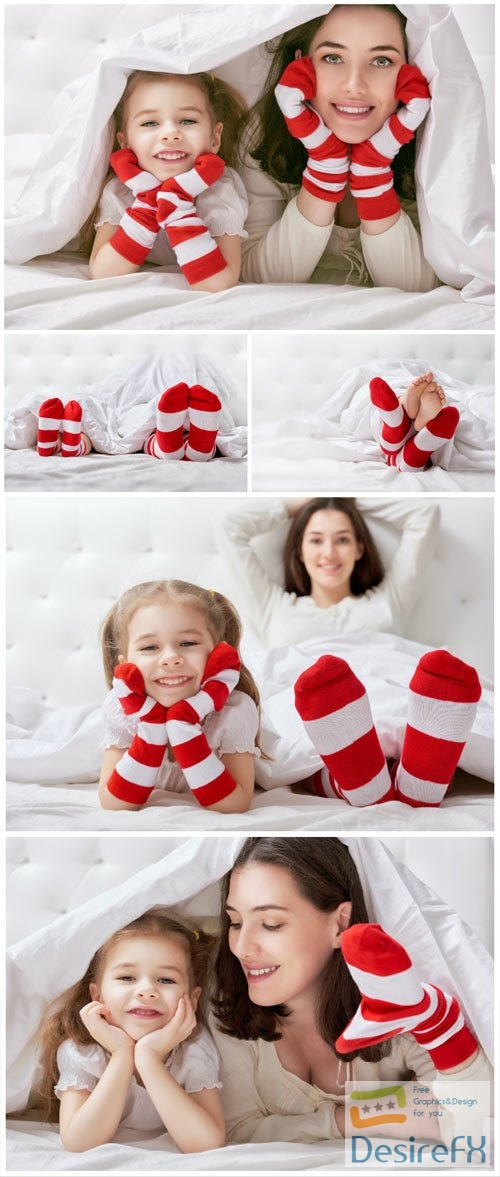 Cheerful little daughter and mom on bed stock photo