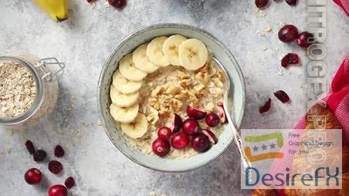Ceramic Bowl of Oatmeal Porridge with Banana Fresh Cranberries and Walnuts
